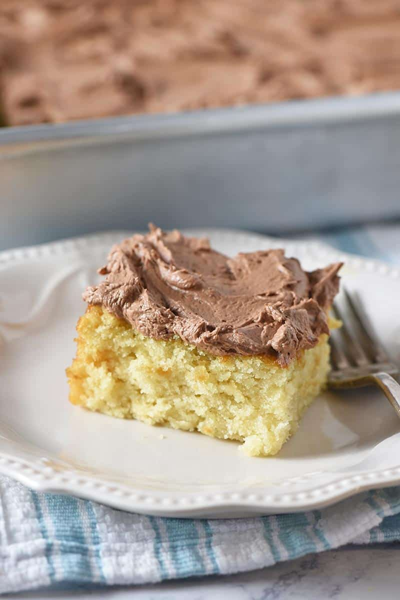 slice of yellow cake with chocolate frosting on white plate with fork