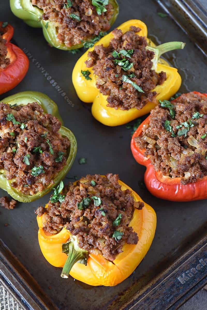 sloppy joe stuffed peppers on baking sheet, garnished with fresh basil
