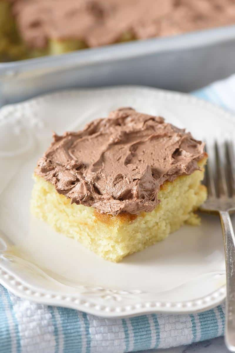 piece of yellow cake with chocolate buttercream frosting on ivory plate with fork