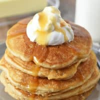 butterbeer pancakes from scratch on gray plate with whipped cream on top and butterscotch syrup