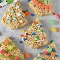 decorated Christmas tree Rice Krispie treats on white marble background with candies and holiday kitchen towel