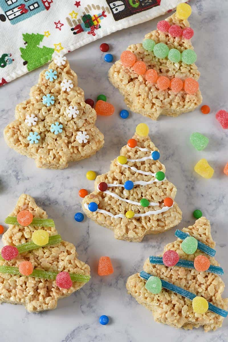 decorated Christmas tree Rice Krispie treats on white marble countertop with candies and holiday kitchen towel