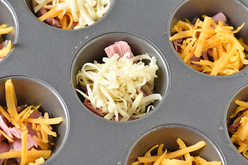 adding cheese with ham to muffin cups for breakfast egg muffins