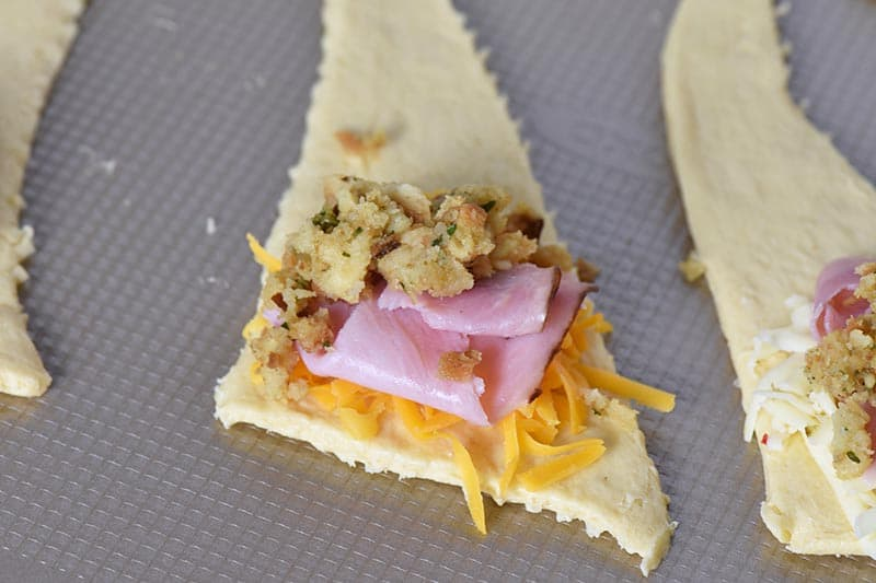 making leftover ham and stuffing crescent rolls on cookie sheet