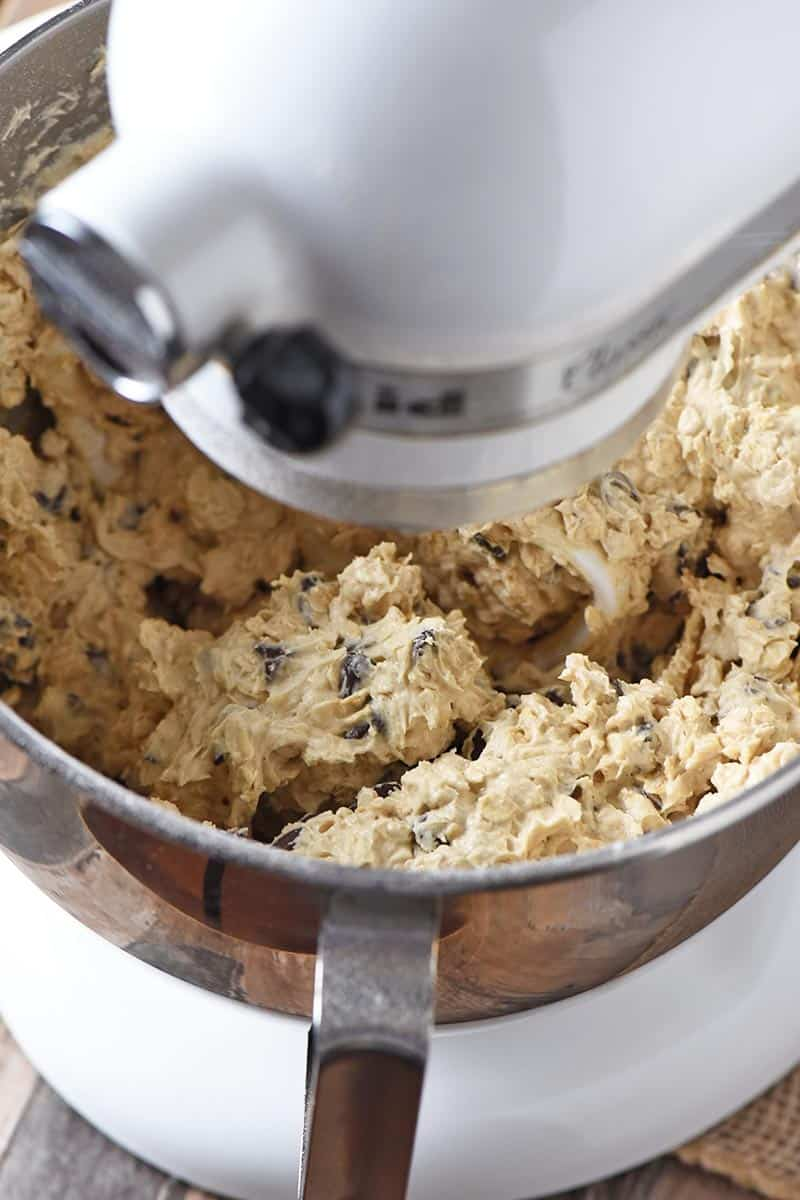 mixing up oatmeal chocolate chip cookie dough with rolled oats in white KitchenAid mixer