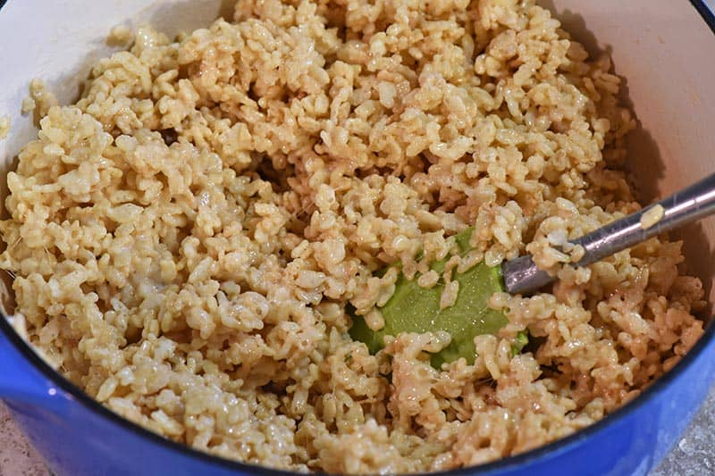 making Rice Krispies cereal into Rice Krispie treats in blue Dutch oven