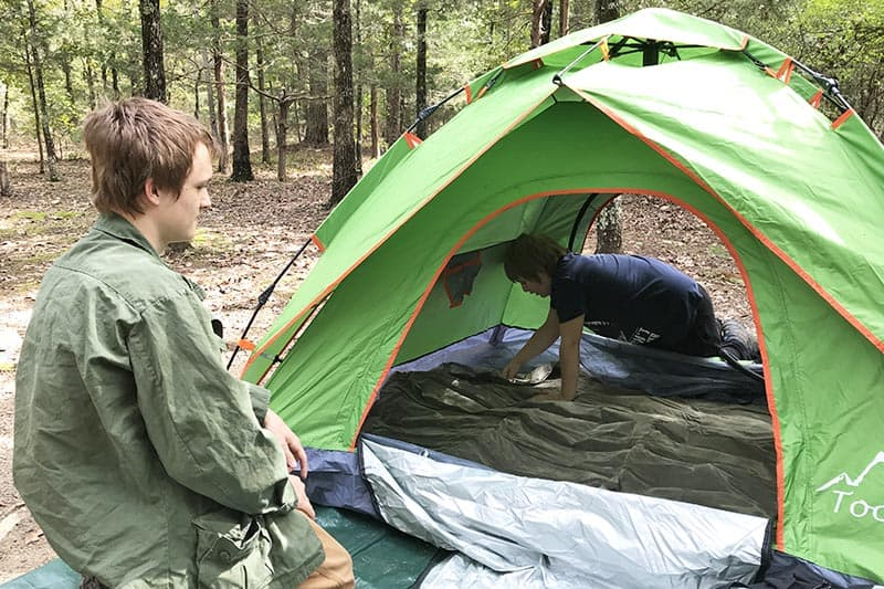 boys airing up the air mattress in a green pop up tent at Petit Jean State Park