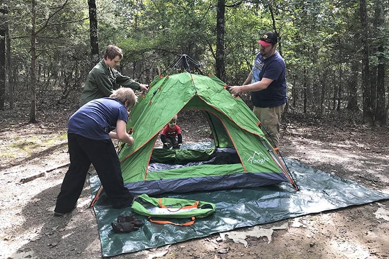 setting up a green pop up tent in Petit Jean State Park Campground in Arkansas