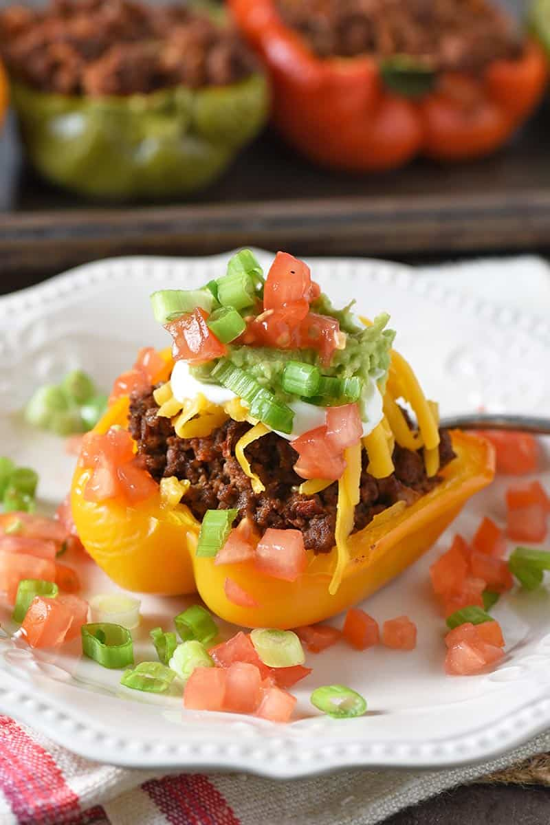 ground beef taco stuffed peppers, with all the taco toppings, on a white plate