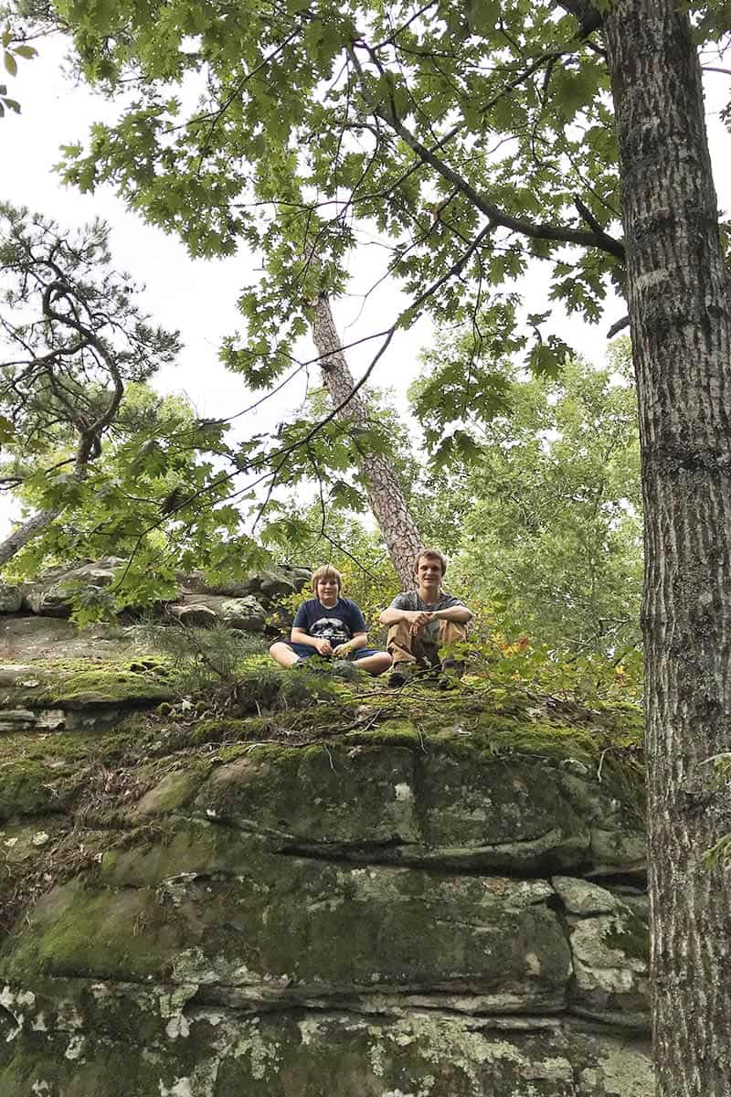 boys sitting on boulder along Bear Cave Trail in Petit Jean State Park, Arkansas