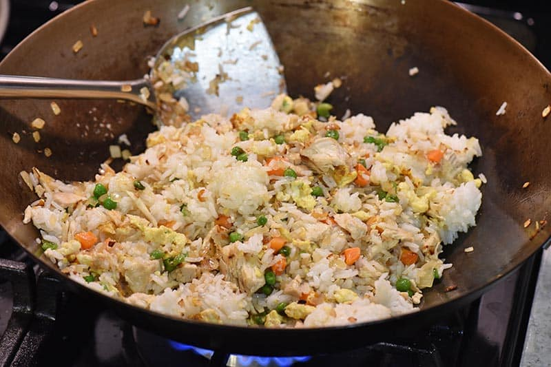 stir frying rice into chicken fried rice recipe in large wok with metal spatula