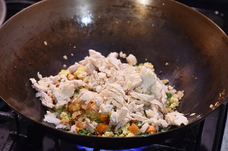 stirring chicken into chicken fried rice mixture in large wok