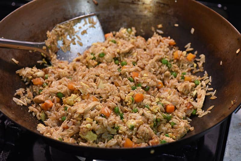 stirring chicken fried rice together in large wok with large wok spatula
