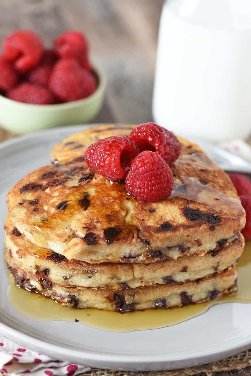 stack of heart shaped chocolate chip pancakes from scratch on gray plate with raspberries and maple syrup