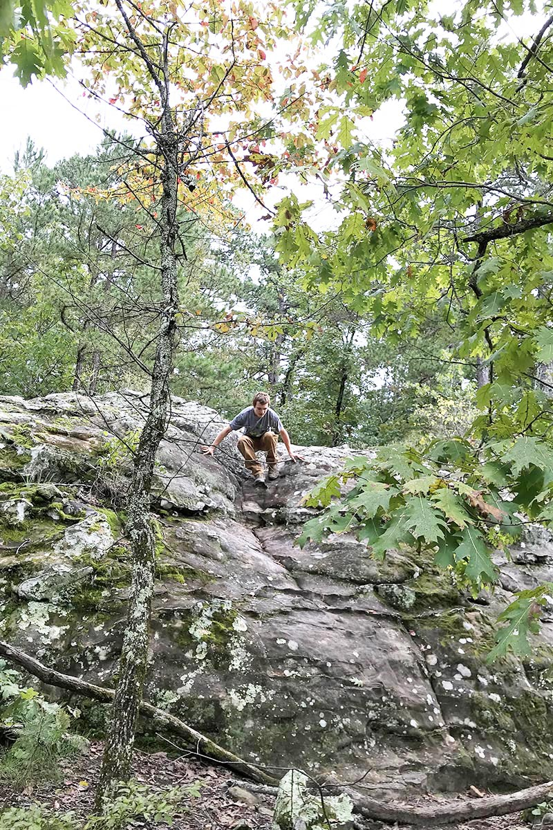 climbing around on gigantic boulder and rock formations on Bear Cave Trail in Petit Jean State Park, Arkansas