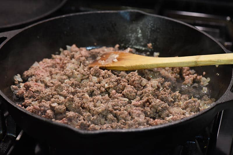 cooking ground beef for tater tot hamburger casserole in cast iron skillet