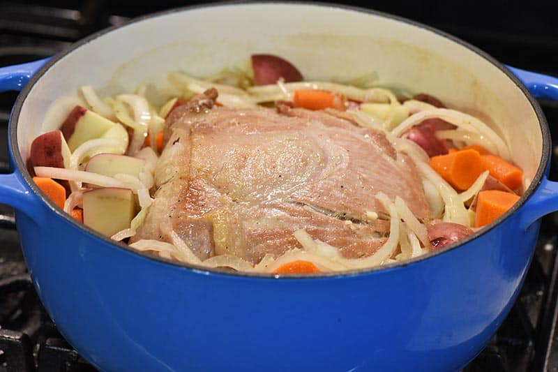 cooking pork roast with vegetables in blue Dutch oven