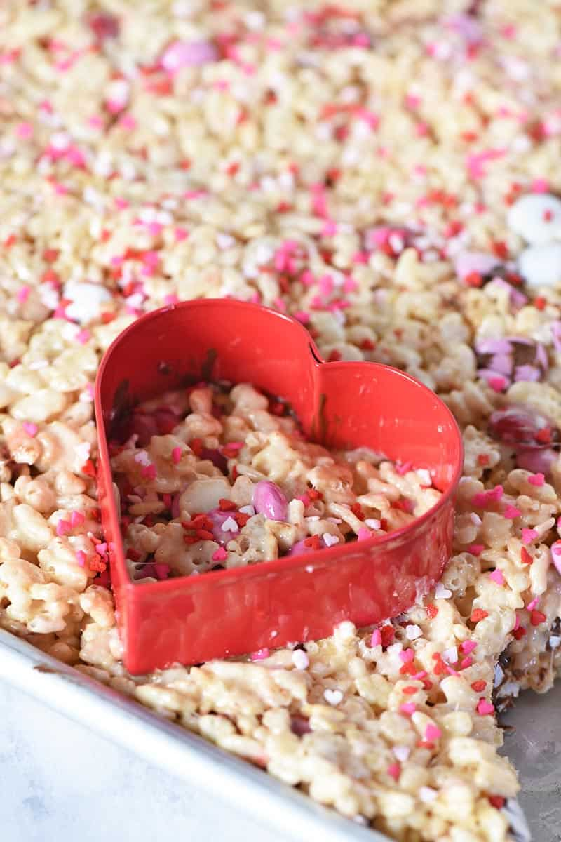 cutting heart shaped Rice Krispie treats with red heart shaped cookie cutter in brownie pan