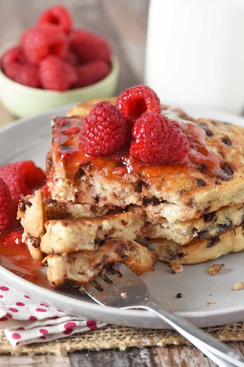 fork and bite of heart shaped chocolate chip pancakes with raspberries and sauce on gray plate