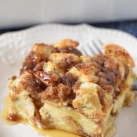 slice of French toast casserole on white plate with maple syrup and fork