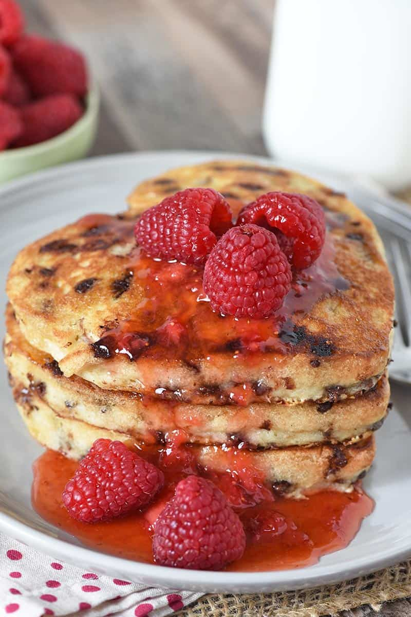 heart shaped chocolate chip pancakes stacked on gray plate, slathered with raspberries and strawberry jam