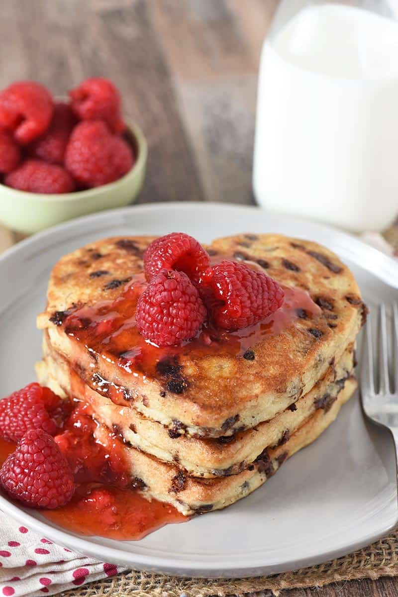 heart shaped pancakes with chocolate chips, raspberries, and sauce on gray plate