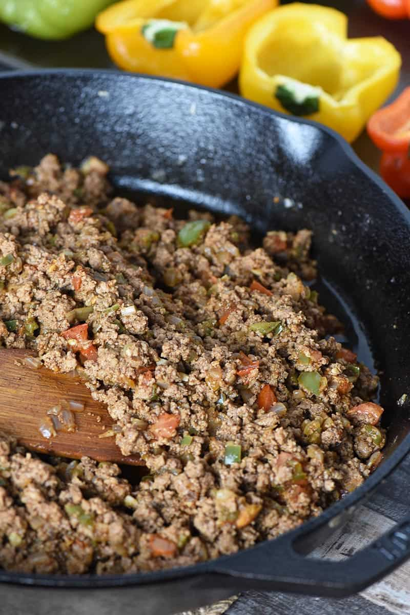 ground beef taco meat in cast iron skillet and prepared bell peppers for taco stuffed pepper recipe
