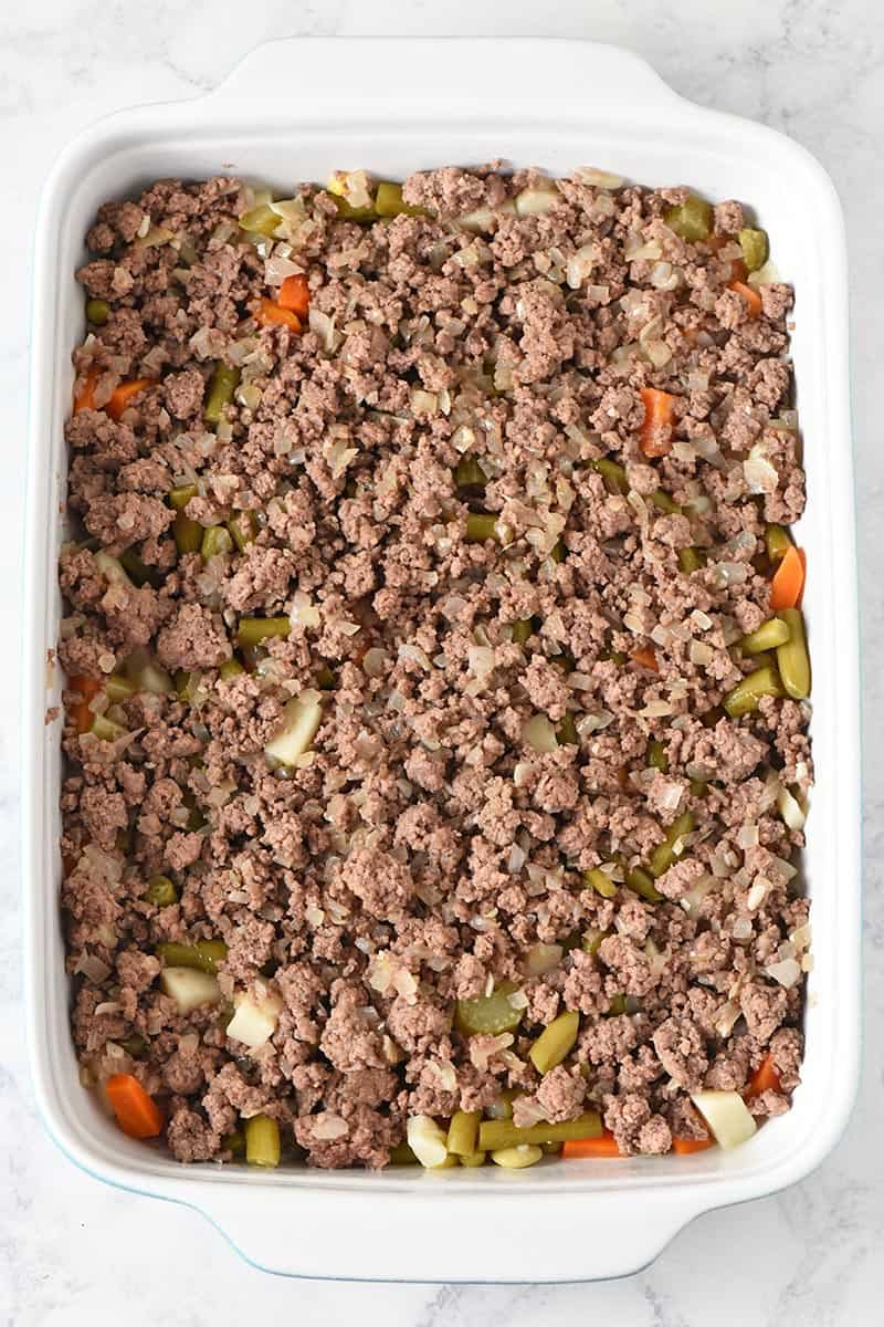 layering browned ground beef in blue and white casserole dish for tater tot casserole recipe