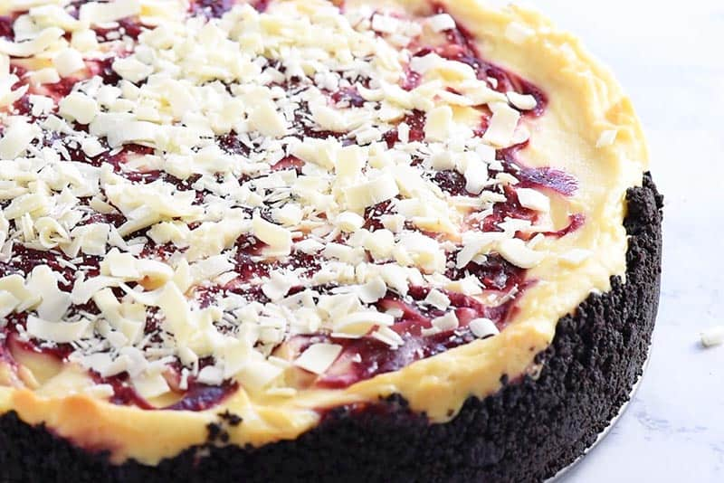 sprinkling shredded white chocolate onto top of white chocolate raspberry cheesecake