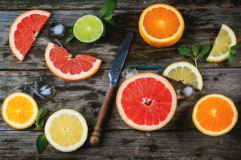 Citrus fruits on a cutting board with a knife