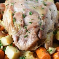 pork roast in oven with potatoes and carrots in a cast iron pan