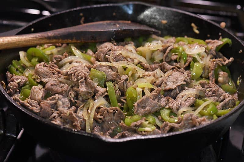 cooking Philly cheese steak meat with vegetables in cast iron skillet with wooden spatula