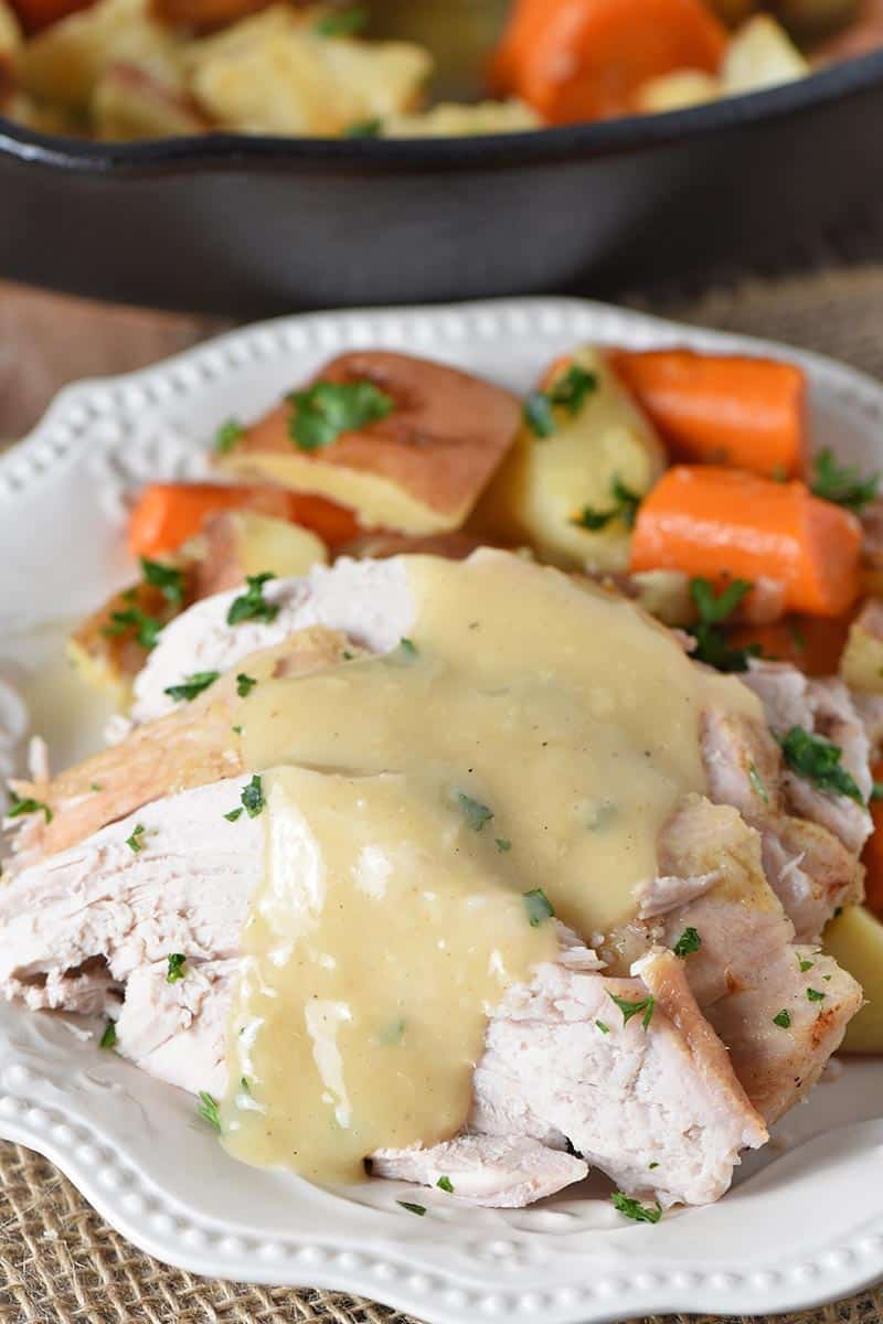 pork roast with vegetables and gravy on white plate