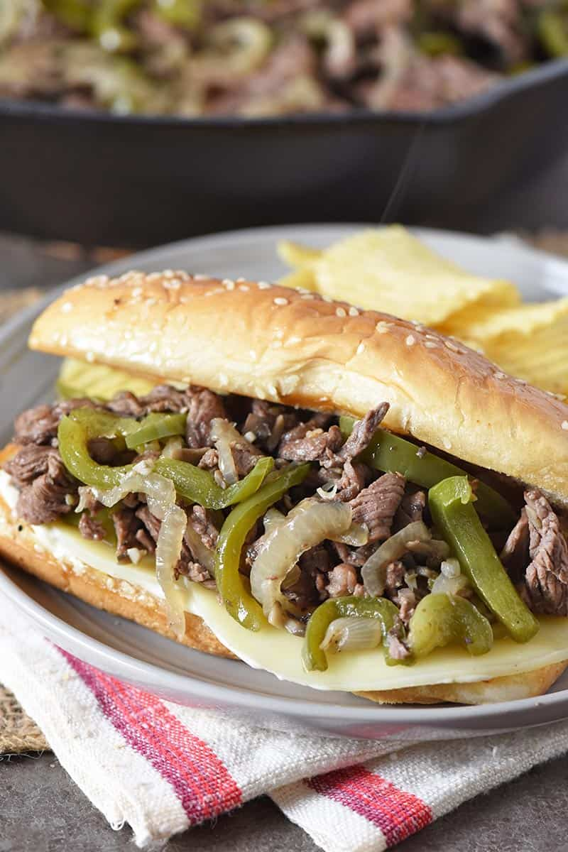Philly cheesesteak sandwich with provolone cheese, served on gray plate with potato chips