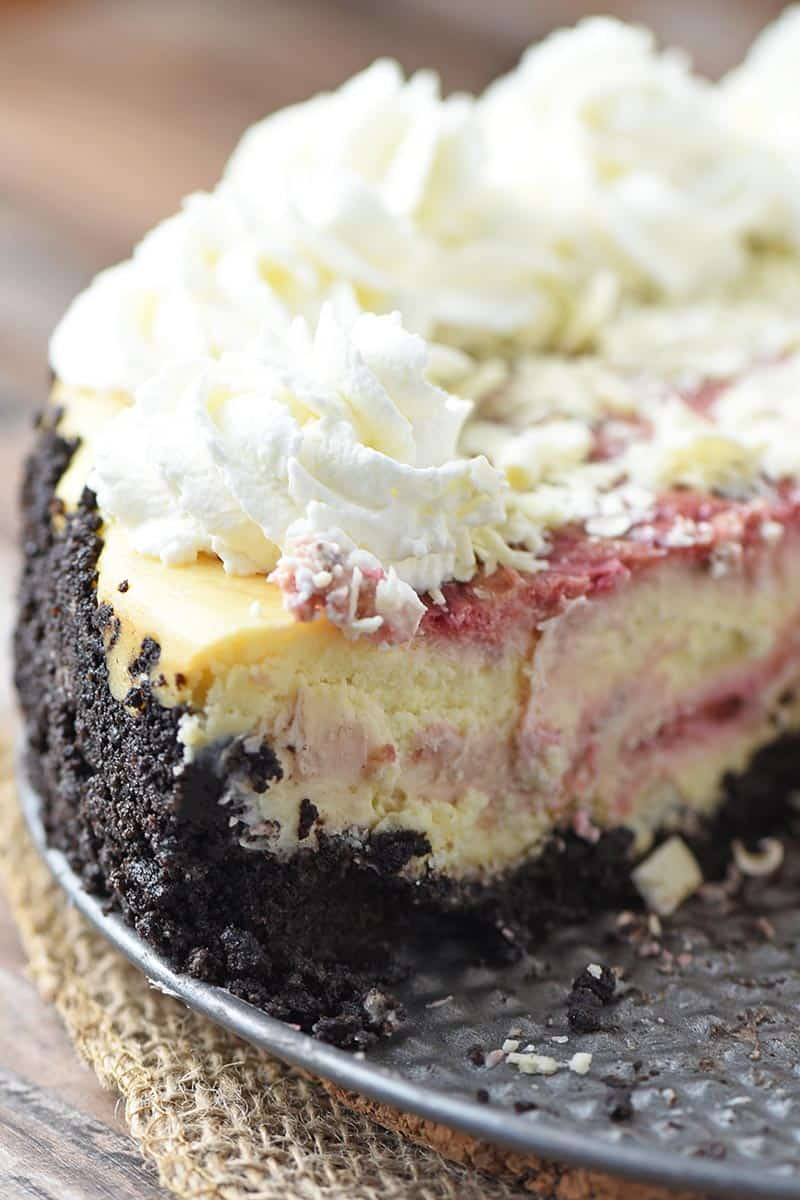 sliced white chocolate raspberry cheesecake with a raspberry swirl and chocolate cookie crust