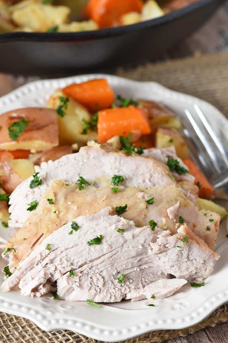 sliced pork roast with vegetables on white plate