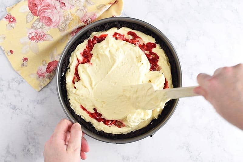 adding second half of raspberry cheesecake batter to springform baking pan with a spatula