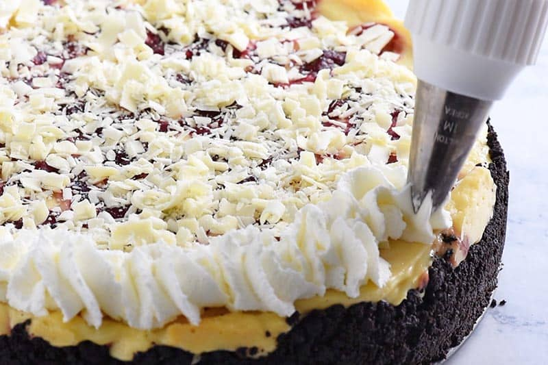swirling whipped cream onto white chocolate raspberry cheesecake with cake tip