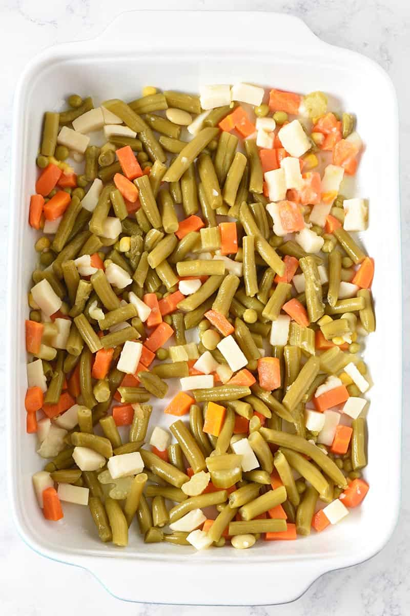 layering canned green beans and mixed vegetables to make tater tot casserole with veggies in blue and white casserole dish