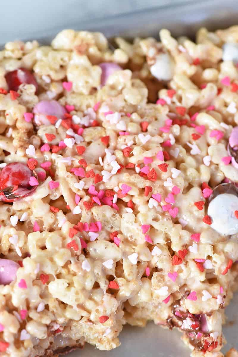 adding heart shaped Valentine sprinkles to Rice Krispie treats, making Valentine's Day treats