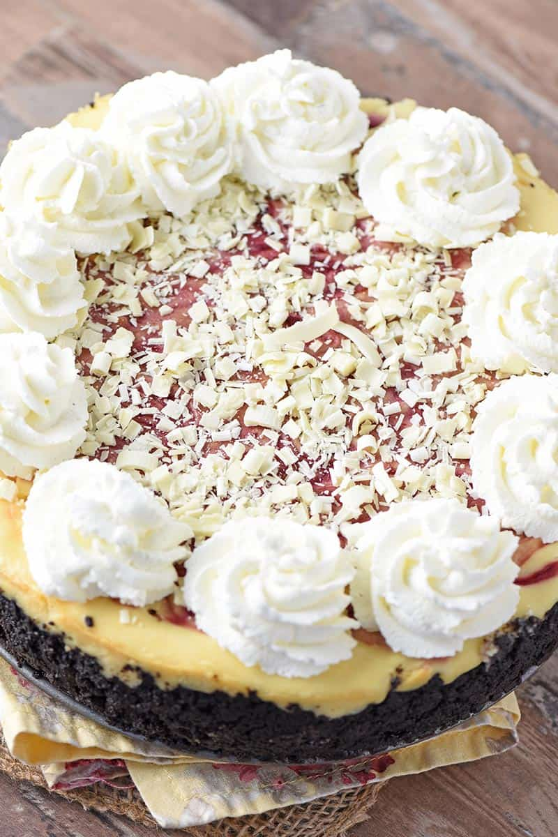 whole white chocolate raspberry cheesecake with white chocolate flakes and swirls of whipped cream on top