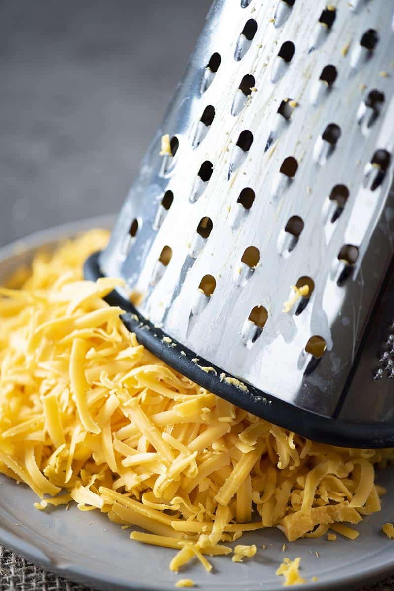shredded cheese on gray plate with cheese grater