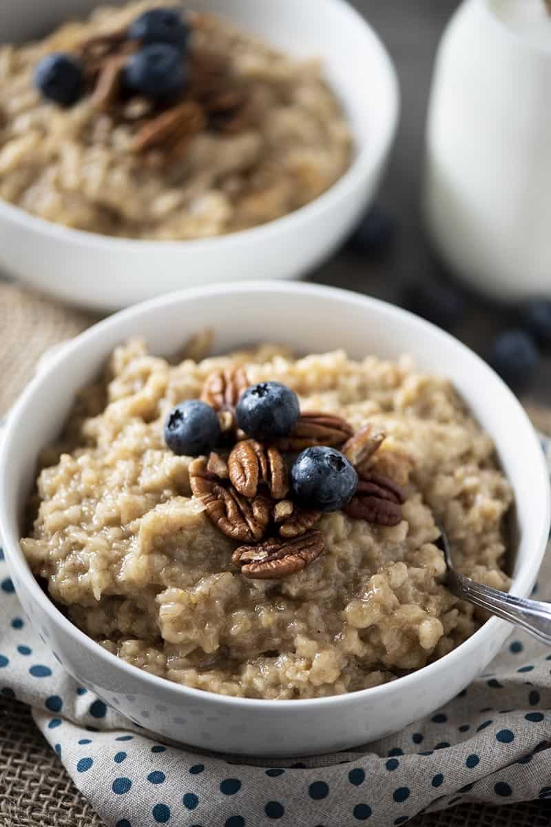 white bowl of maple brown sugar oatmeal with blueberries and pecans