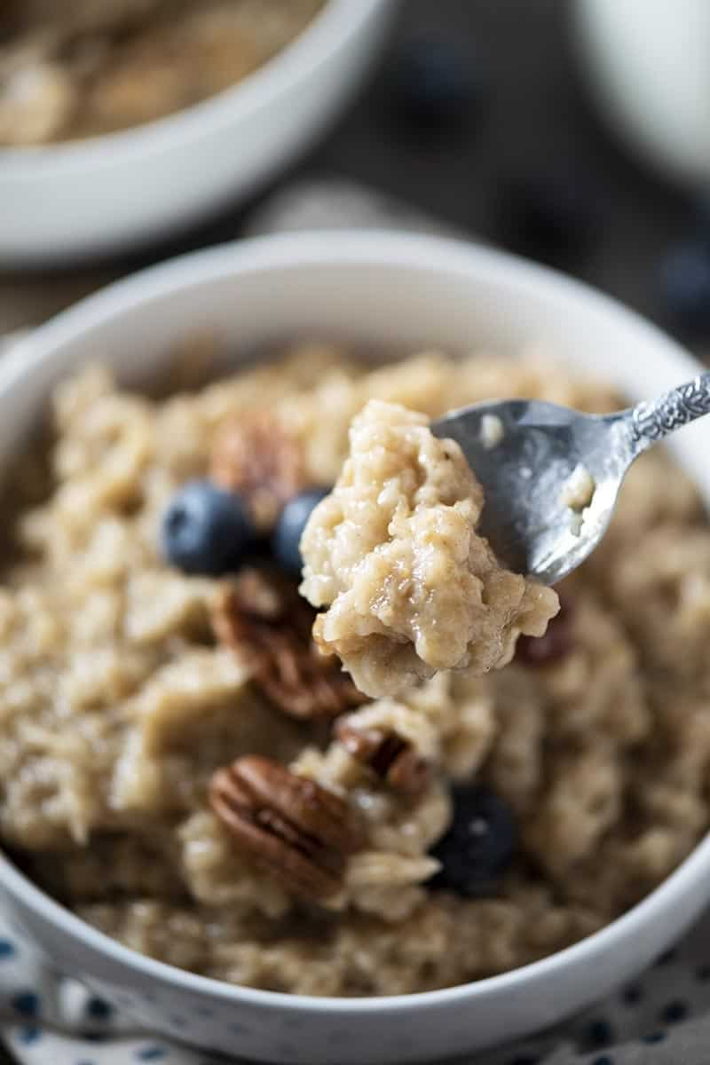 spoonful of maple and brown sugar oatmeal above white bowl of oatmeal with pecans and blueberries