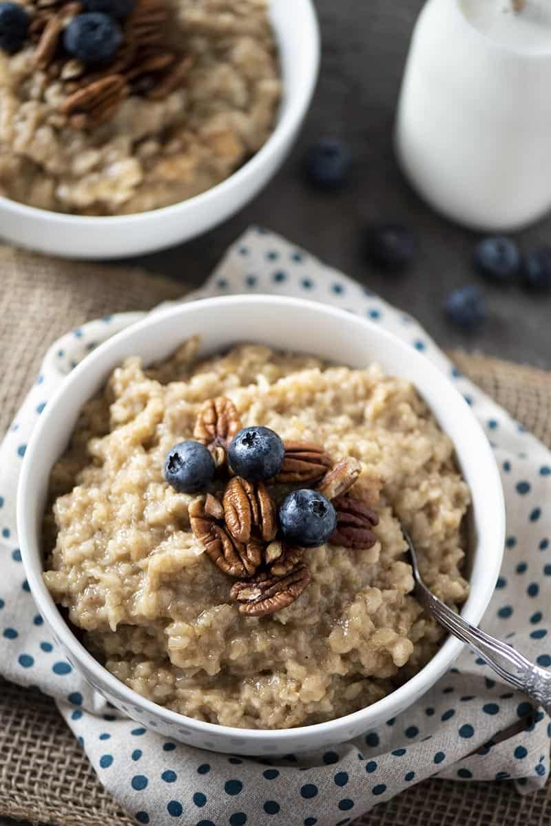 maple oats in white bowl with spoon, pecans, and blueberries