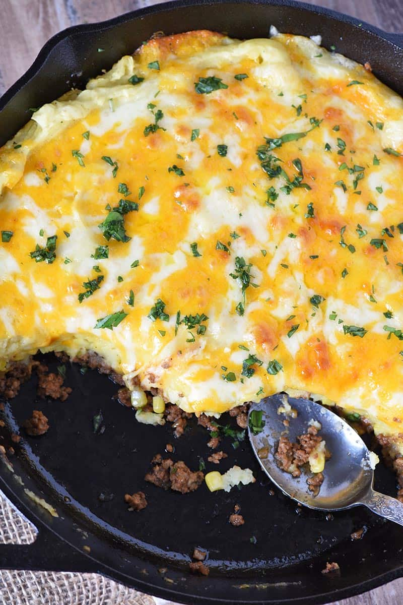 shepherd's pie with ground beef, covered with melted cheese, in a cast iron skillet with a large spoon
