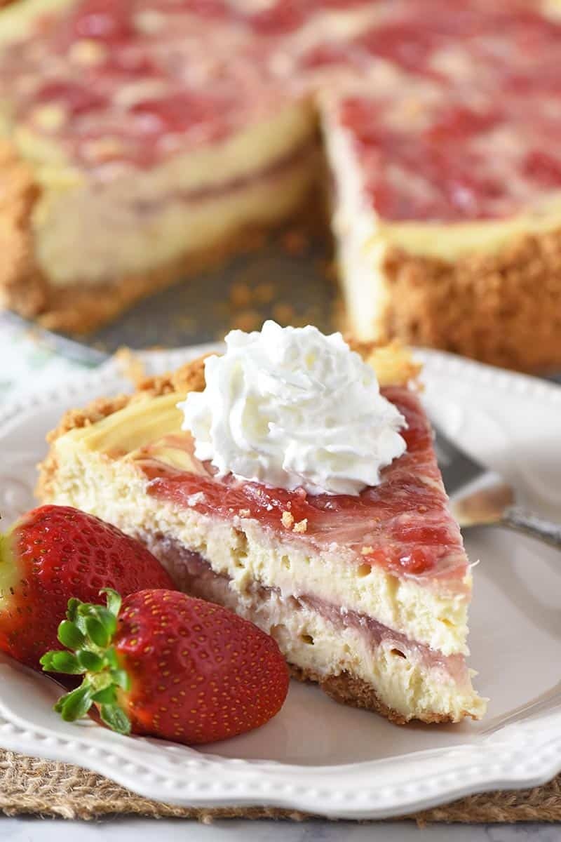 slice of strawberry swirl cheesecake with whipped cream and fresh strawberries on a white plate
