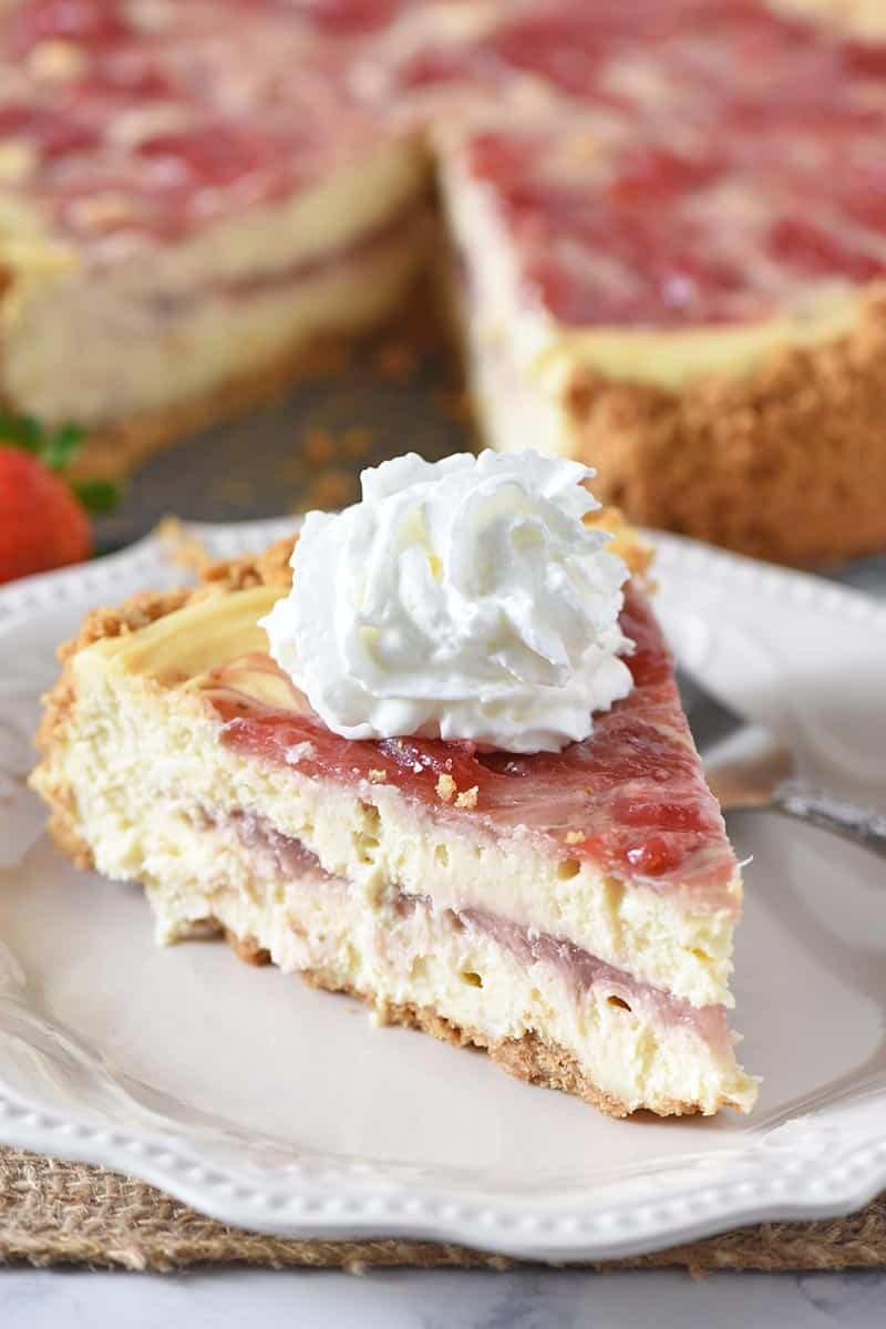slice of strawberry swirl cheesecake on white plate with whipped cream and a fork