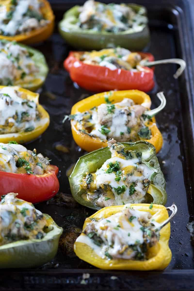 baked low carb stuffed peppers with chicken on baking sheet, sprinkled with parsley over melted cheese