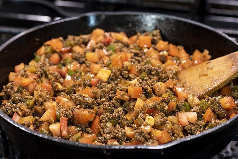 cooking ground beef mixture for taco tater tot hotdish in cast iron skillet with wooden spatula